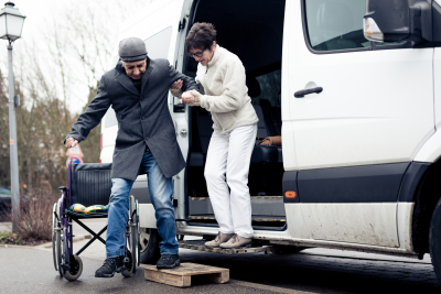 an elderly man assisted by a woman to unboard on van