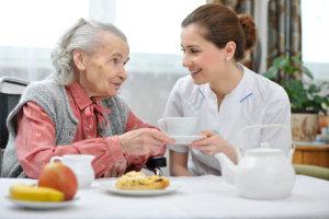 Elder having tea with caregiver