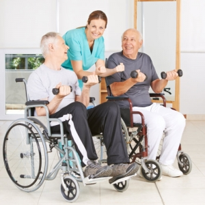 physiotherapist with two senior men in wheelchairs